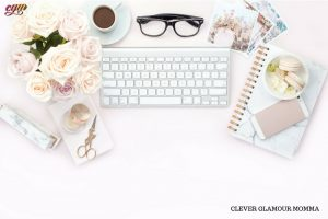 Branded Computer on desk with glasses, flowers, scissors, notebook & cup of coffee. Clever Glamour Momma