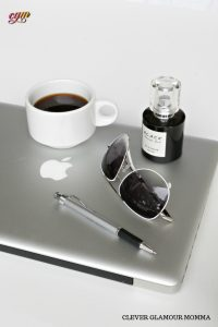 Branded Apple Computer with sunglasses, pen, cup of coffee and ink on top. Clever Glamour Momma